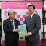 橋本教育長(右)に教材を手渡す長嶋専務